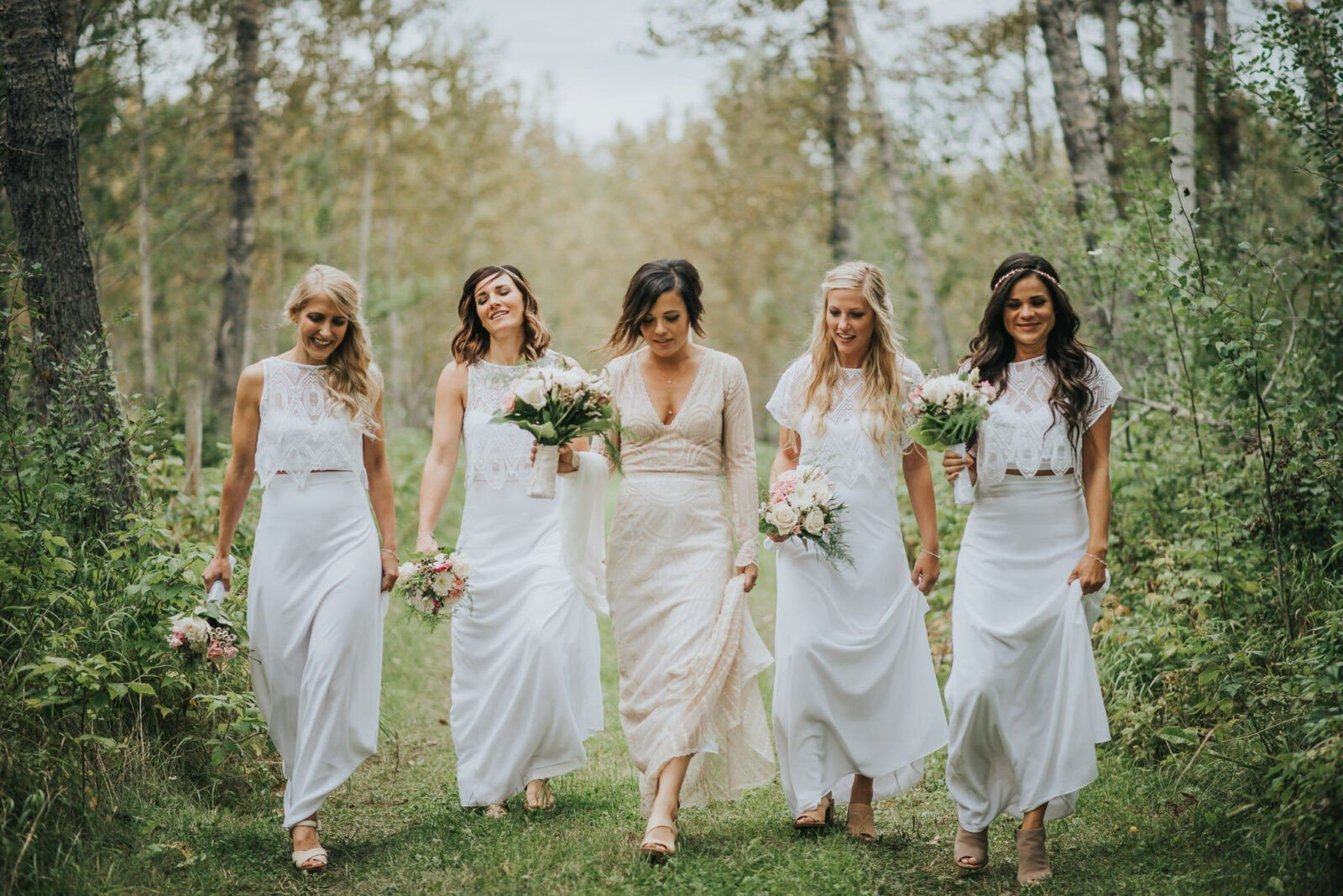 Bridal party walking through forest in custom dresses.