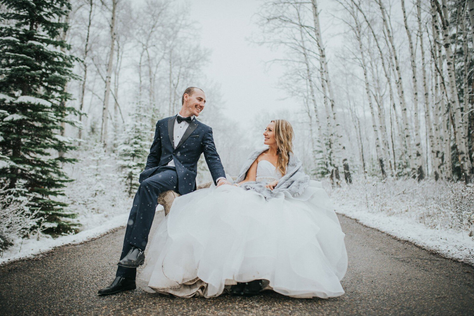 Bride and groom in magical snowstorm near pyramid lake in Jasper National Park