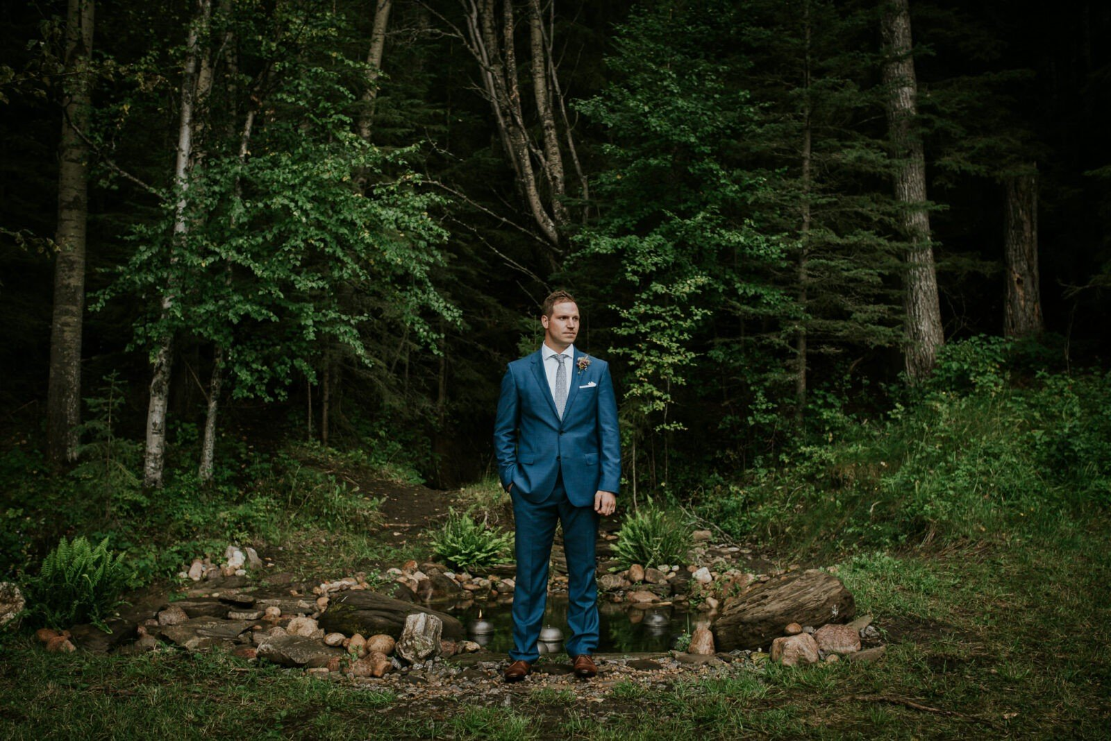 Blue suit groom in the forest.