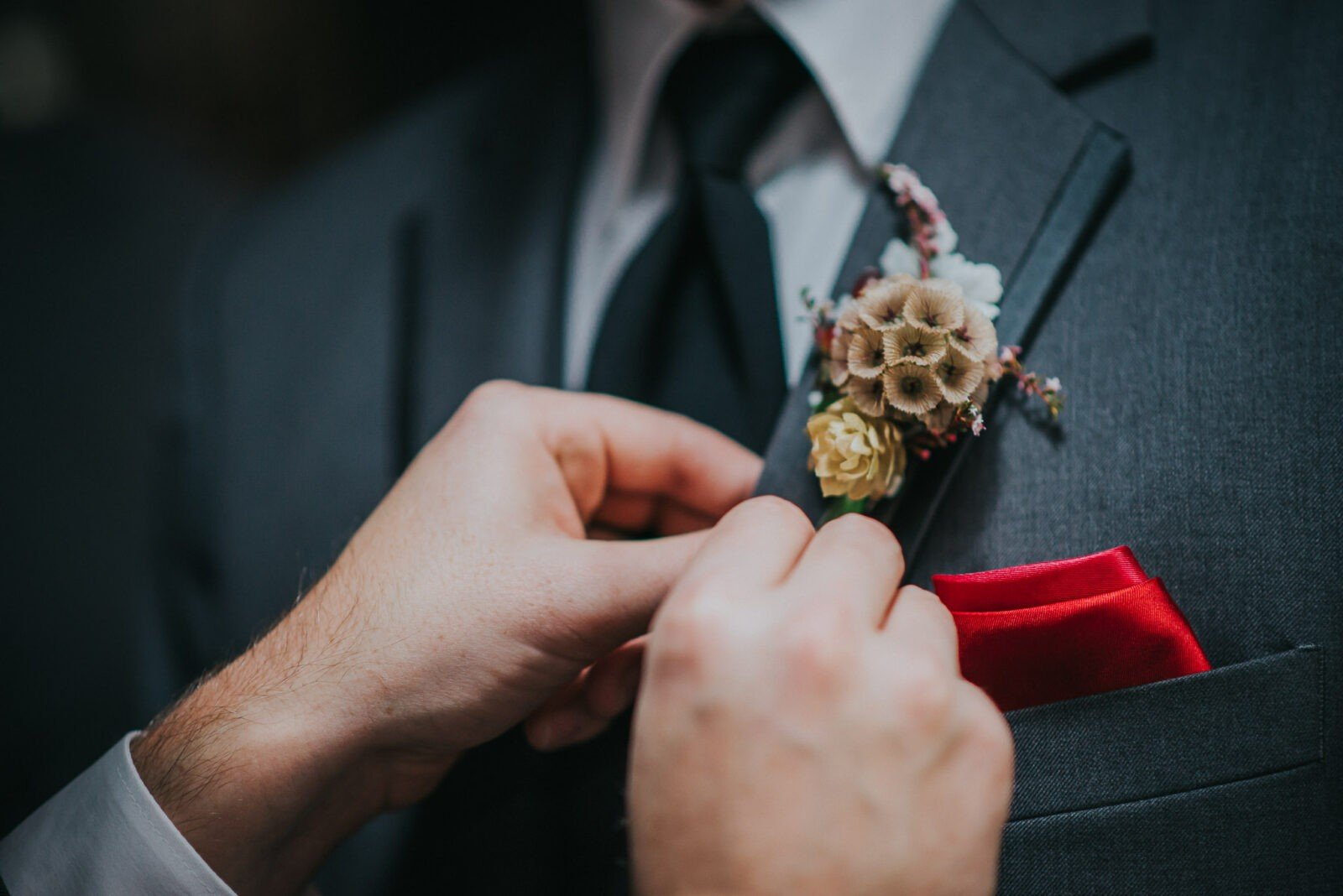 Groom putting on the boutonnierre